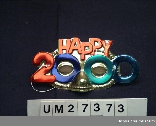 """Ögonmask av  formpressad gulfärgad plast i upphöjd relief, färgad i rött, grönt och blått med texten:""""HAPPY 2000"""". Runt resårband. På ömse sidor om ögonöppningarna är placeratde en tvåa resp. en nolla så att maskens form bildar siffran 2000.  Oanvänd i skyddsförpackning. Inköpt på Timari  i Uddevalla för 9:50.   För information om Millennieinsamlingen, se UM27360."""