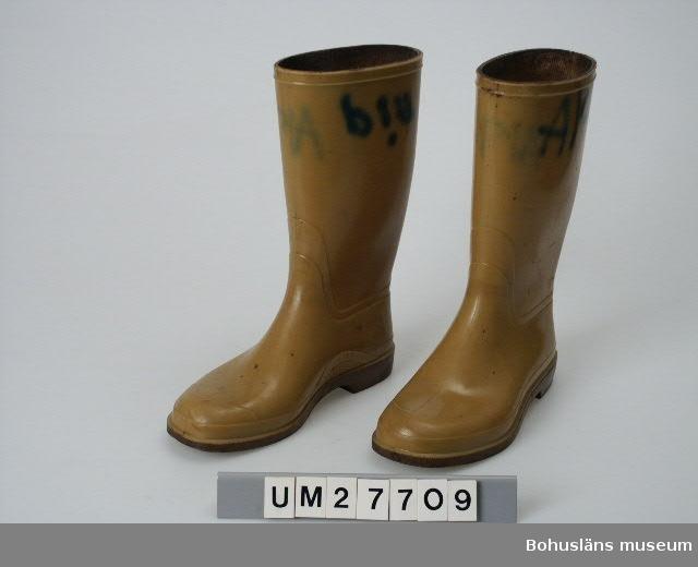 """Ett par gula stövlar av PVC-plast med brungul refflad sula och med insida av tyg. Storlek 37 Den ena märkta""""A19"""" och den andra """"PIA"""" med grön tuschpenna på utsidan och insidan av stövelskaftet. Mögliga och smutsiga.  Mjukgörare i plasten lämnar ytan och har gjort materialet kladdigt. Fiskebröderna AB startade på 1920-talet under namnet: Bröderna Kristiansson & Co. För ytterligare bakgrund, se även UM27702.  Materialet är insamlat av Bohusläns museum i februari 1988 i samband med att konservfabrikens byggnader revs.  Material om konservindustrin i Bohuslän är arkiverad under: Dokumentation- och Kulturminnesvårdsavdelningen med seriesignum M7D.  Litteratur: Ur hav till burk  och kartong. Fiskberedningen i Sotenäs kommun. Projekt Sverige i Blixtbelysning. Kungshamns Dokumentationsgrupp, Bohusläns museum 1996, se särskilt  s. 16-17, 23-24 Bohusläns samhälls- och näringsliv. 4. Konservindustrin.  (1983)  Bohusläns museum, Etnologiska institutionen vid Göteborgs universitet, Landstinget i Göteborgs och Bohus län, se särskilt s. 36 - 40, 71"""
