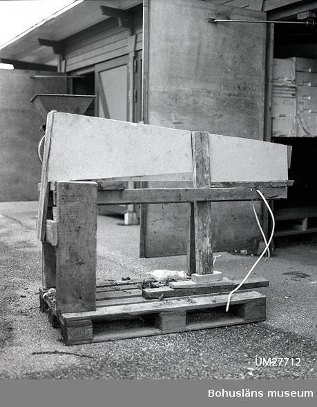 Mångformig, mindre kvarn av gjutjärn, grönmålad. Fyrkantigt konad tratt, drivhjul hörande till remdrift på ena sidan. Kvarnen har suttit fastskruvad i ena änden av  en specialtillverkad avlång, kraftig grönmålad träbänk, ca L 150 cm, B 100 cm och H 150 cm. Undertill har varit placerad en remdrift för drivhjulet, sedermera övertäckt av ett enkelt skydd av vitmålad tretex-platta. Kvarnen har varit elektrifierad under senare år. Kvarnen är mycket rostig och det gröna färglagret flagar.  Bänken är fotodokumenterad och gallrad. Sv/v negativ i Bilagepärmen UM27712. Till kvarnen hör också två lösa trattar, UM27712:2-3.  Fiskebröderna AB startade på 1920-talet under namnet: Bröderna Kristiansson & Co. För ytterligare bakgrund, se även UM27702.  Materialet är insamlat av Bohusläns museum i februari 1988 i samband med att konservfabrikens byggnader revs.  Material om konservindustrin i Bohuslän är arkiverad under: Dokumentation- och Kulturminnesvårdsavdelningen med seriesignum M7D.  Litteratur: Ur hav till burk och kartong. Fiskberedningen i Sotenäs kommun. Projekt Sverige i Blixtbelysning. Kungshamns Dokumentationsgrupp, Bohusläns museum 1996, se särskilt  s. 16-17, 23-24 Bohusläns samhälls- och näringsliv. 4. Konservindustrin.  (1983)  Bohusläns museum, Etnologiska institutionen vid Göteborgs universitet, Landstinget i Göteborgs och Bohus län, se särskilt s. 36 - 40, 71.