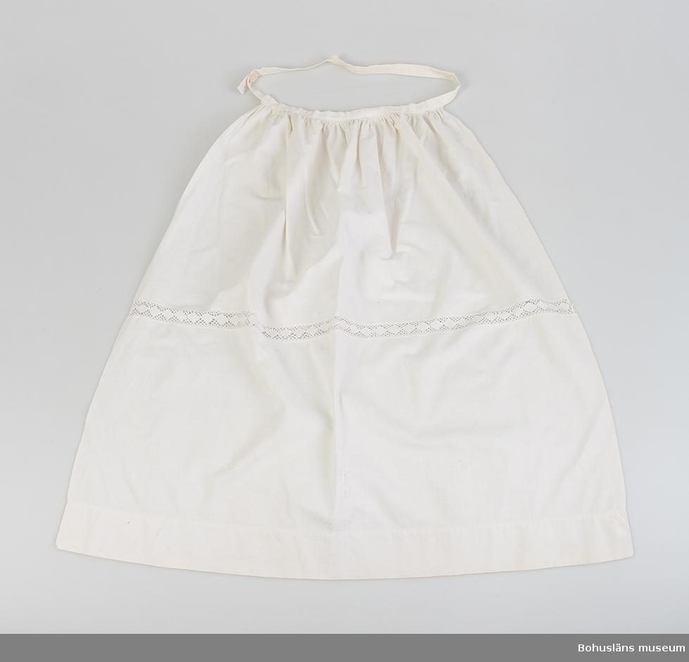 Förkläde av vit finvävd bomull. Mitt på förklädet infälld 20 mm  bred spets, maskinknypplad med väv- och nätbotten.  I midjan är förklädet rynkat mot ett påsytt dubbelvikt förklädesband som knäpps i vänster baksida med knapp i knapphål. Några stoppningar, några hål och missfärgningar.