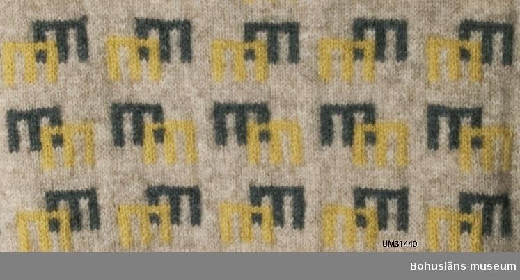 """Stickad jumper med långa ärmar, naturvitt ullgarn. Framstycket täckt av mönster i gult och grått mot det naturvita,  troligen är det Stående grinden.  Formgivare Emma Jacobsson. Enligt företagets mönsterförteckning komponerades """"Stående grinden"""" före år 1947. Originaletikett: Bohus Stickning Ett antal hål, mindre lagningar gjorda av brukaren.  För upplysningar om förvärvet, se UM031434.  Litt: Häglund, U. med bidrag av Ingrid Mesterton. Bohus Stickning. Bohusläns museums förlag 1999. Keele, W. Poems of Color. Knitting in the Bohus Tradition. And the women who drove this Swedish cottage industry.  Interweave press 1995."""
