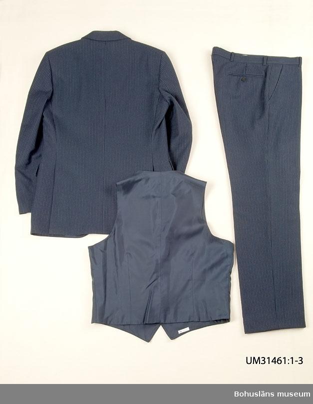 """Mörkblå kostymkavaj (UM31461:1) sammanhörande med kostymbyxa (UM31461:2) och kostymväst (UM31461:3). 410 Mått ärmlängd 42 cm.  Mörklblå ull med smala kritstreck.  Enkelknäppt med två knappar framtill, djup ringning. Infälld bröstficka på vänster sida, två fickor med ficklock fram.  I ryggen mittsöm, sprund i sidorna, baktill bildande vad som i folkmun brukar kallas """"dasslock"""".  Knapphål på vänster slag. Fyra knappar på vardera ärm. Fyra invändiga fickor. Fodrad med mörkblå satin, ärmarna med vit randvävd satin. Passpoalstickningar runt kavajens kanter. TygHängare i nacken med vävda texten: MADE IN SWEDEN Firmaetikett i tyg på innerfickan texten:  """"TIGER OF SWEDEN"""" Firmaetikett i ena innerfickan, texten:  """"TIGER OF SWEDEN STORL. SIZE. GRÖSSE  B 48. 451 26 UDDEVALLA"""