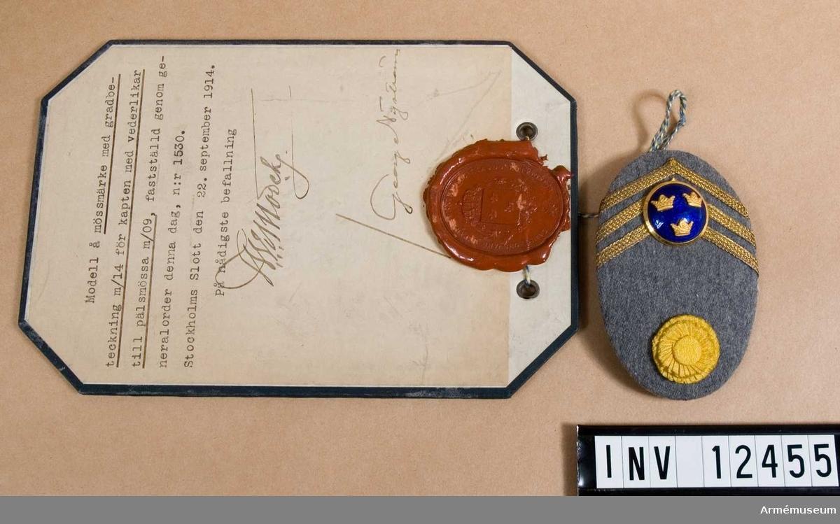 Grupp C I. Modell på mössmärke med gradbeteckning m/1914 för kapten med vederlikar till pälsmössa m/1909.  Från intendenturens modellkammare.