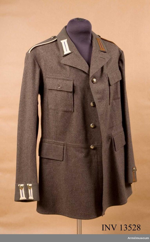Grupp C I.  Vapenrock av gråbrungrön kommiss, tunnare. Kavajslag, krage, axelklaffar och ärmuppslag av kläde.