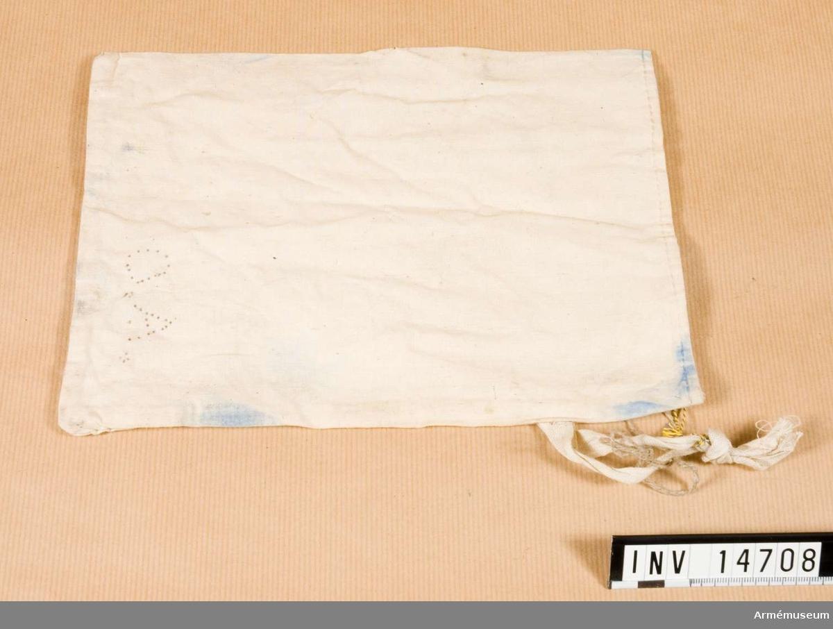 """Grupp C II För dagens proviant. Av vitt bomullstyg 25 cm lång och 18 cm bred, med två  fastsydda bomullsband vid sidorna för att stänga påsen. På påsen finns två bokstäver """"G.A.""""."""