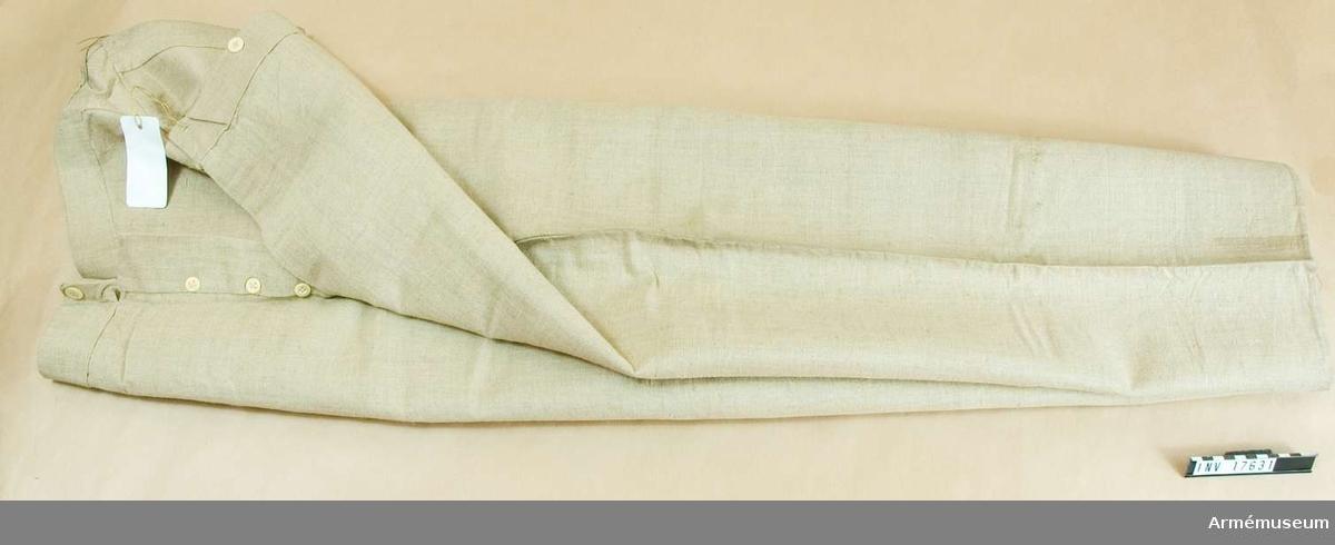 """Grupp C I. Byxor av grov grå linnelärft, långa med två fickor på sidorna och en liten för klocka, sprund med fem benknappar, fyra knappar för hängslen. Fickorna är av grov grå lärft. Byxorna  har en halvrund stämpel - oläslig. Dessa byxor användes troligen för dagligt bruk av meniga inom kasernområdet. De har en pappersetikett, på vilken det står: """"Equipements Militaires. Chaveau & Blanc Fils, Successeurs de Blanc Ainé, Rue des Petits Hotels 26 & 28, Lafayette, Paris"""". På andra sidan finns ett svart sigill med påskrift: """"Pantalon de toile"""" (linnebyxa) """"2 poches, 3 tailles"""" (två fickor, tre tillskärningar Fr. 3.30 (troligen pris). Enl kapten W Granberg."""