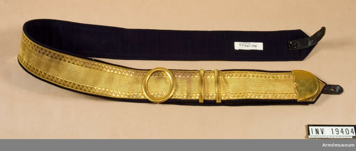 """Av guldgalon och med mörkblått kläde och förgyllda beslag.  Enligt etikett """"Kapt. Graeve"""", varför man kan förmoda att detta är ägarens nman."""