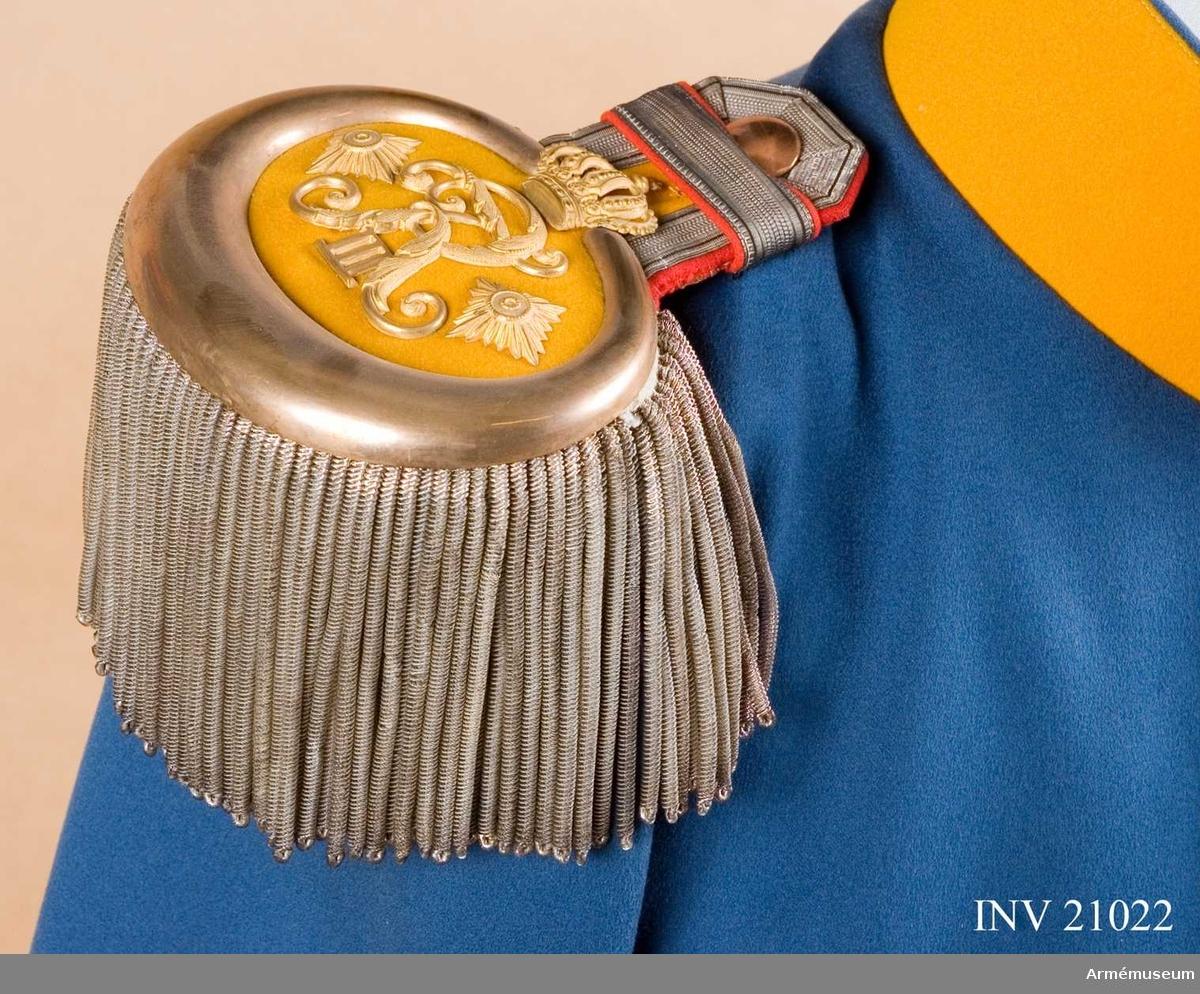 Grupp C I. Ur uniform för överste vid Dragonregementet König Friedrich III 2. schlesiska, nr 8 VI Armékåren, Tyskland. Består av syrtut, vapenrock, ridbyxa, långbyxa, överrock, hjälm, mössa, skärp, kartusch, bandolär, axelklaffar, sabel med balja och portepé.Epåletter med citrongul klädesmatta och en guldplåt runt om nederdelen. På övre delen av epålettenhalsen en silvergalon, b:10 mm. Epåletterna är fodrade med citrongult kläde. De har konungens namnchiffer (Fredrichs Rex III) med krona och två stjärnor och runt densamma guldbuljoner. Buljoner och stjärnor =överstes grad.Enl W Granberg.