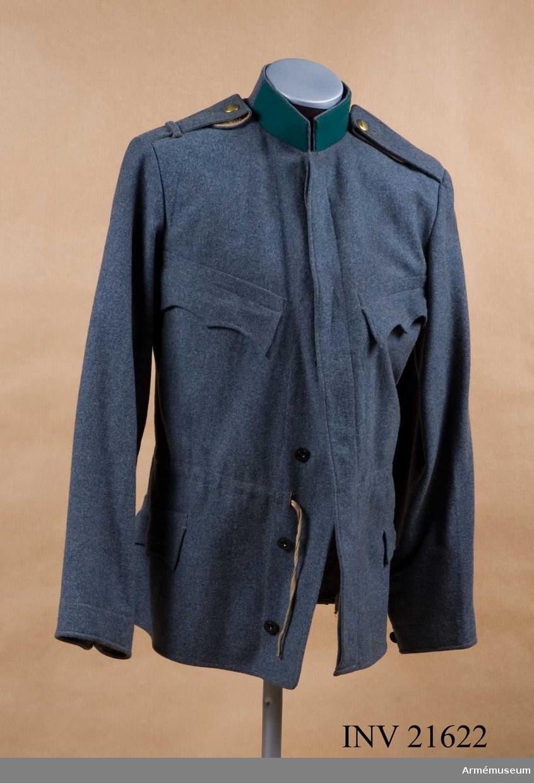 Grupp C I. Ur uniform för alpjägare m/1868-1908, Tyrolskt kejsarjägar- regemente i Österrike.  Består av mössa, vapenrock, byxor, skor, ränsel, livrem med väskor. Blus av ljusgrått kläde. Enradig med 6 knappar, dold knäppning. Axelklaffar av kläde, b:55 mm. Fickor, två sidofickor och två bröstfickor med treuddiga lock. Foder endast på rockens övre del, svart vaddfodrad. Krage, upprättstående av kläde med raka vinklar. Den har två klaffar av gräsgrönt kläde (tyrolska jägarfärgerna).