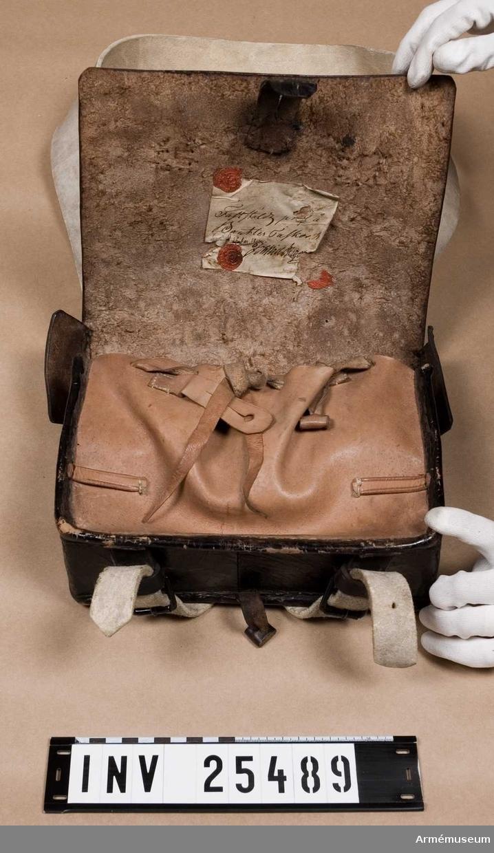 """Grupp C I. Ur uniform för manskap vid indelta infanteriet; 1816-1829. Består av jacka, byxa, tschakå, pompong, kordong, vapenplåt, skärp, halsduk, patronkök, bandolärrem, skor, damasker, bajonettbalja. Köket reparerades och överfördes hit år 1888 från museets övertaliga. Modellapp på insidan av locket: """"Fastställd prof å Bantler Taskor Stockholm d. 26 Apr 18(oläsligt)""""."""