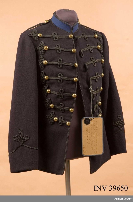 """Grupp C I. Vidhängande modellapp: """"Modell å Attila af mörkblått kläde att tjena till efterrättelse enligt General Order denna dag, No 726. Stockholms Slott den 31 oktober 1872. På Nådigste Befallning O. Weidenhielm / Hugo Raab"""". Med 2 lösa kragar."""