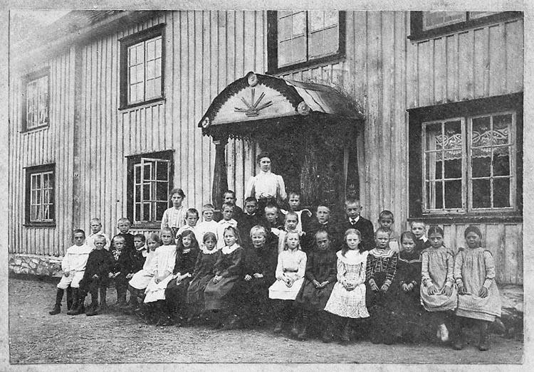 """Enligt fotografens journal nr 8 1951-1957: """"Småskolan 1906, i Västergård, Stenungsund Enligt fotografens notering: """"Småskolan i Västergård. Fr. Selma, Stenungsund""""."""