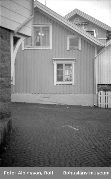 """Enligt fotografens noteringar: """"Friberg"""" en av de sista som bor nere i hamnen året runt. Arne Häller, som han heter, spejar ut från sitt fönster. Han får passa på att sova nu för på sommaren får han ingen ro.""""  Fototid: 1996 den 12 januari."""