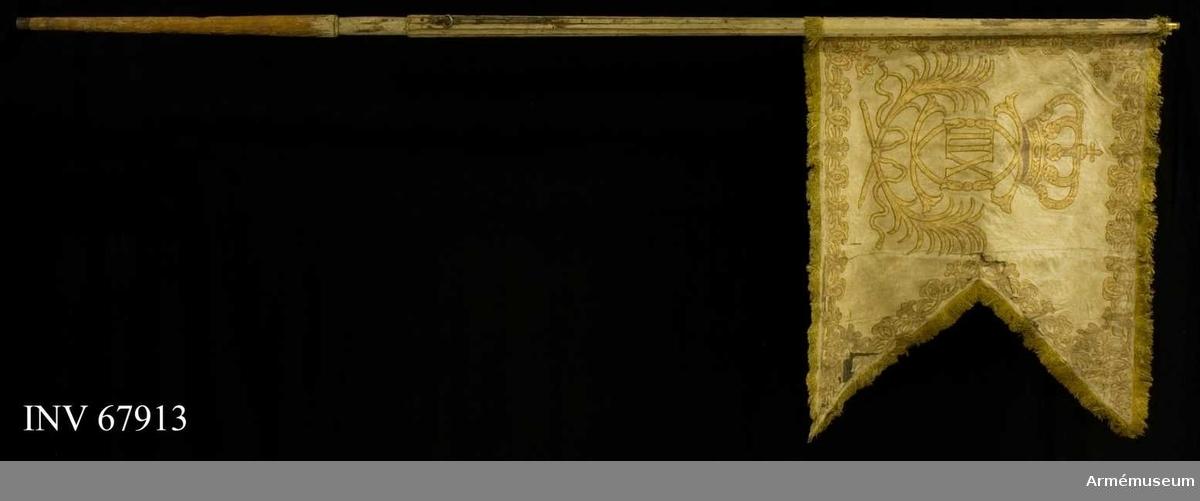 Duk: Tillverkad av enkel vit sidendamast. Tvåtungad. Sydd av två horisontella våder. Kantad med gul silkesfrans. Fäst vid stången med tre rader tennlickor på vita sidenband.  Dekor: Målat omvänt lika på båda sidor i guld, Karl XII:s namnchiffer, dubbelt C under sluten rödfodrad krona. Omgiven av två palmkvistar, nedtill korsade och hopbundna med rosett.  Längs kanten bård av palmkvistar och ornament liknande dubbla C samt i hörnen inåtvända öppna kronor.  Stång: Tillverkad av vitmålad furu (ejavsågad), kanellerad. Holk av mässing. Beslagen med tre järnskenor. Doppsko av järn.  Märkning: Rester av spikad lapp.