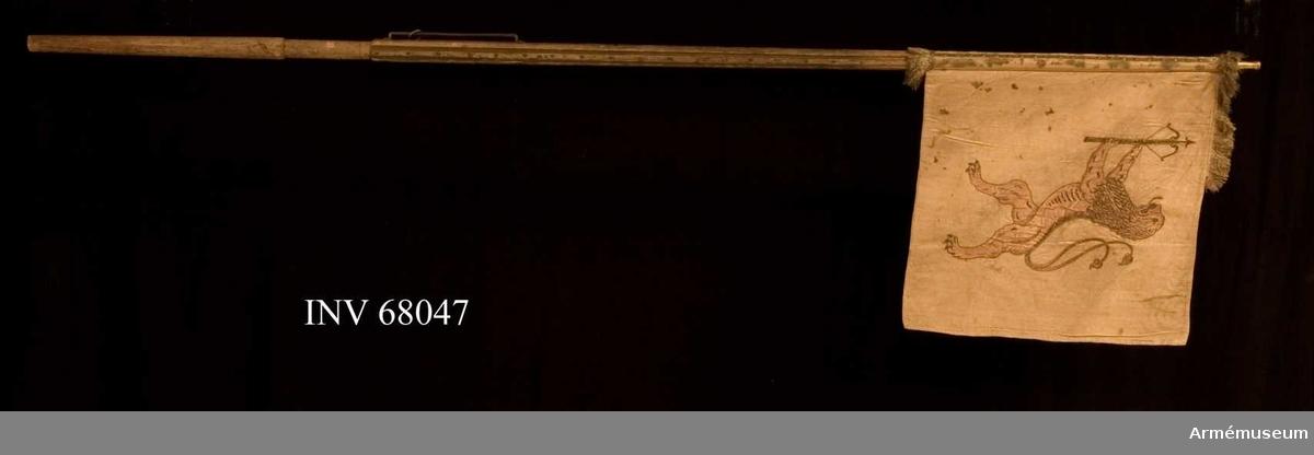 Duk: Tillverkad av dubbel, gul damast, fodrad med lärft. Damasten har ett liksidigt mönster som en symmetrisk spegel. Duken fäst med tre rader tennlickor på silverband.   Dekor: Broderad applikation. På dukens insida ett dubbelsvansat lejon i röd atlas förande ett spänt armborst med pålagd pil i guld och silver. Även ett lejon broderat med guld och silver, konturerna belagda med en snoddsluten kunglig krona, infattat av två nedtill hopknutna lagerkvistar, broderat i silver, högklassiskt broderi.   Frans: Endast rester av en silverfrans återstår.  Stång: Tillverkad av trä, kannelerad, avsågad, vitmålad och förgylld holk finns men ej spets.