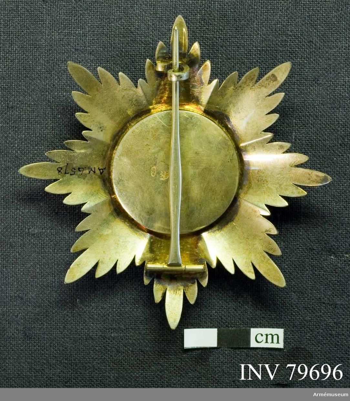 Grupp M.   En silversol, bestående av 8 strålknippen, vart och ett innehållande fem släta, pärlkantade strålar; mellan varje knippe en kort stråle.   I mitten en upphöjd rund sköld, ytterst med en pärlkantad silverram omslutande först ett fött emaljfält, varpå synas dels överst två små flygande, mot varandra vända änglar, hållande en krona och dels devisen: AMAN.PIET.FID. allt i upphöjt silver.   Innerst ett fält av matt, hamrat guld, utgörande underlag för ett rödemaljerat grekiskt, silverkantat kors, vars utseende rönt inflytande av den då rådande rococostilen.  Beskrivning: Carl Peyron.