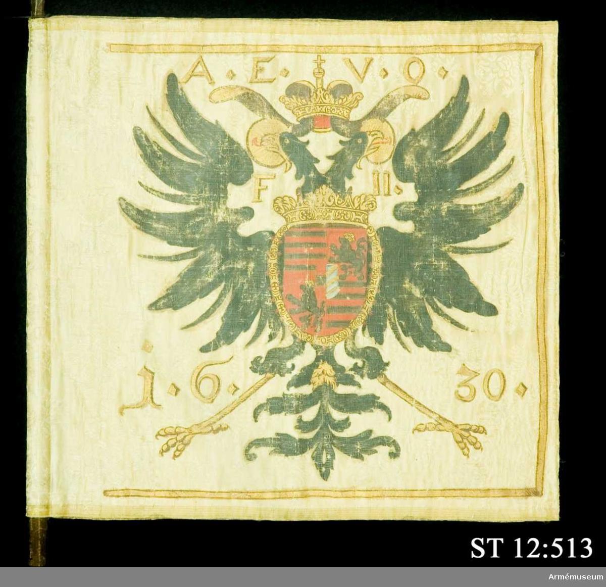 Livstandar. Stång avsågad. Stången är sekundär i två delar.  Inre sidan: Den tysk-romerska dubbelörnen krönt av kejsarkrona. På örnens bröst en vapensköld som innehåller vapnen för Ungern (7-delad sköld i rött och silver) och Böhmen (silverlejon i rött fält) samt en hjärtsköld med Österrikes vapen (silverbjälke i rött fält) och Burgund (styckad sköld i guld och blått) omgivet av Gyllene skinnets ordenskedja.   Yttre sidan: Madonnan med barnet i solstrålekrans.