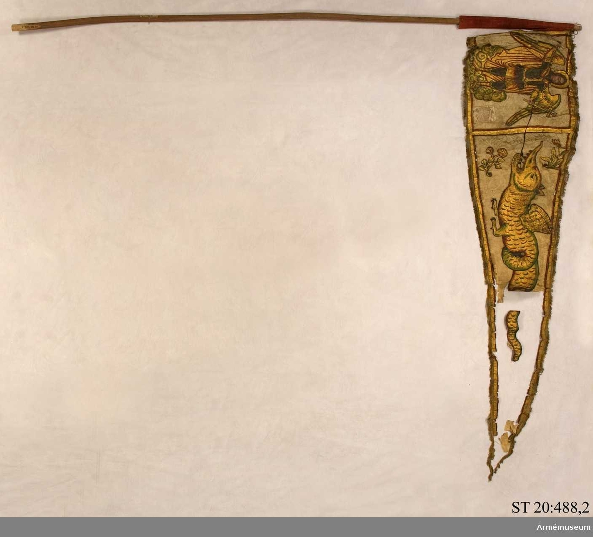 Stående på ett moln S:t Mikael med gyllene vingar och gloria klädd i mantel och rustning av silver och guld  stridande mot en drake.   Mikael håller i höger hand ett spjut och i vänster Kristi kors med pinoredskap.   Drakens huvud är omgivet av två blomsterkvistar.   Runt alla sidor målad bård.