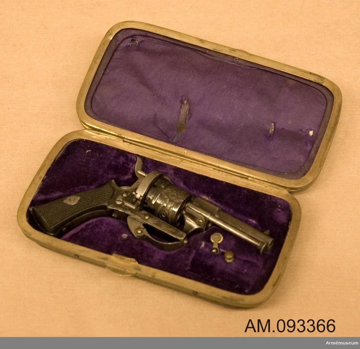 Bär på belgiska stämplar. Förvaras i svart låda fodrad med lila sammetstyg tillsammans med tre stycken cigarrer och fem stycken mindre patroner.