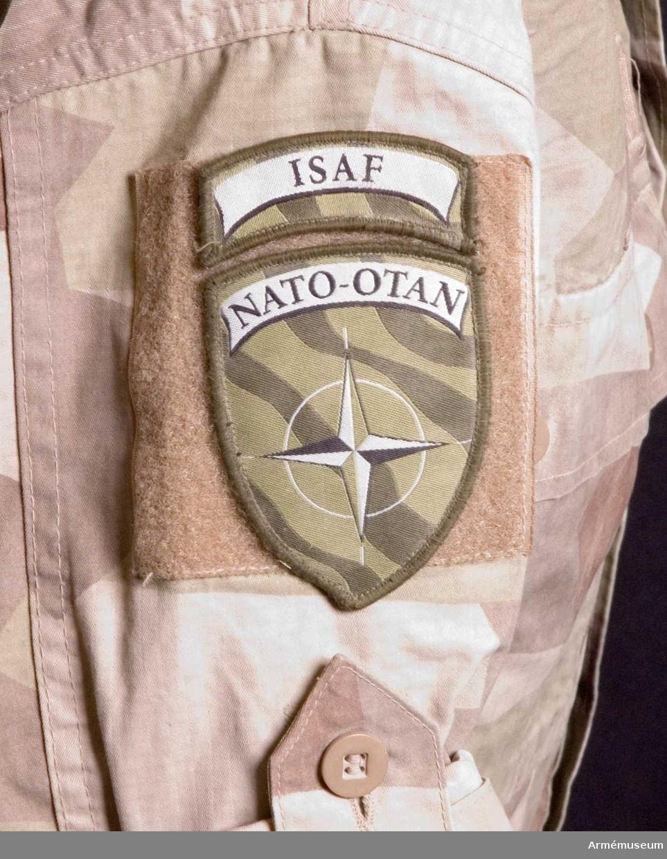"""Utförd i Ökenkamouflage. På vänster ärm: Förbandstecken (Utlandsstyrkan) och Nationalitetsmärke. På höger ärm: """"ISAF"""", """"NATO-OTAN"""". Ovan vänster bröstficka: Namnskylt (Jansson på svenska och arabiska), Nationalitetsmärke och """"ISAF"""". På slaget, mitt fram: Gradbeteckningshylsa för kadett. Tillverkad 2009 i Kina."""