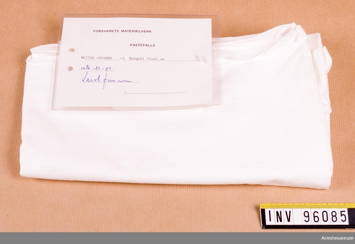 """Vidhängande etikett med text: """"Försvarets materielverk, Fastställs, M7310-031000-5, Örngott 55x65, 1986-03-04 (oläslig underskrift)"""""""