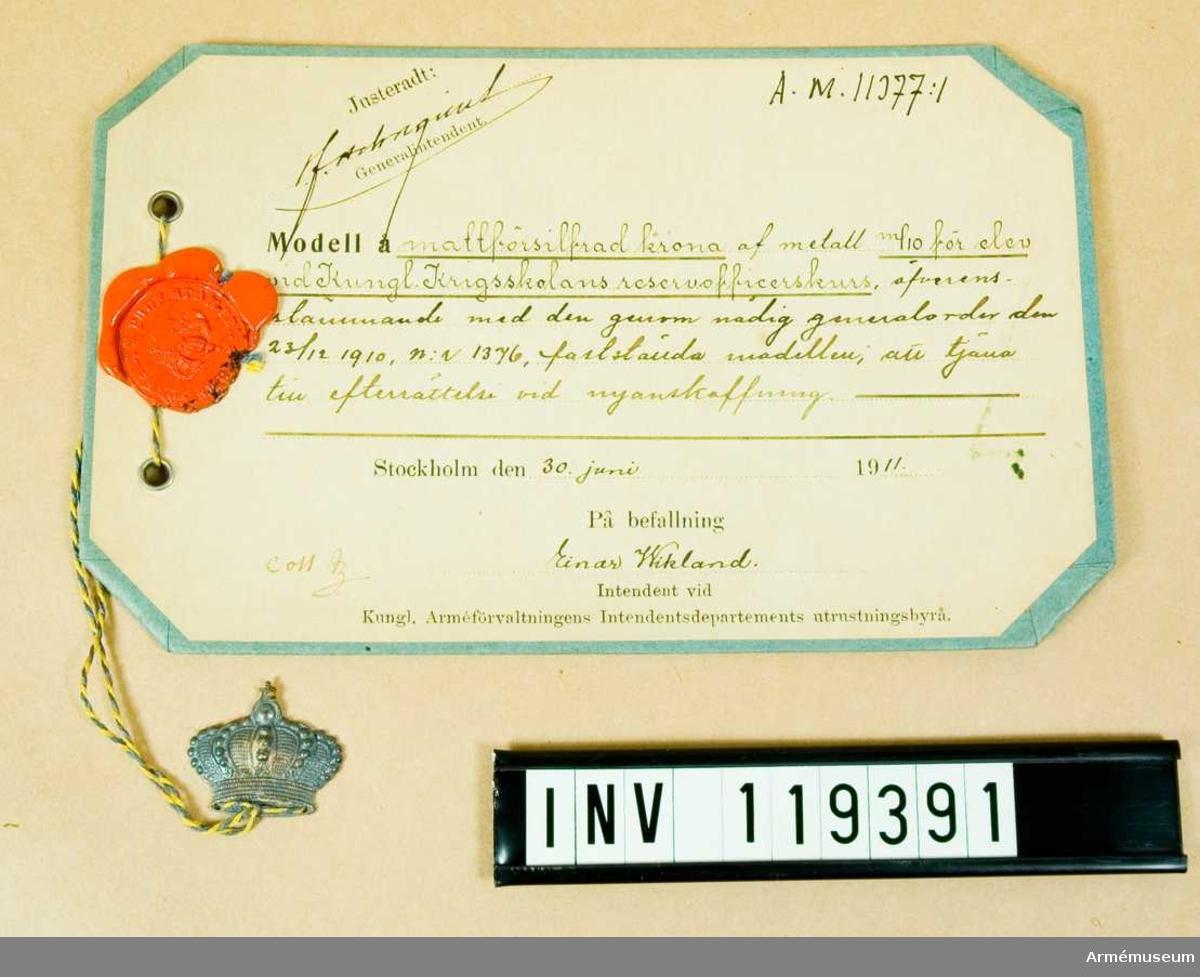 Mattförsilvrad krona av metall m/1910 för elev vid Kungliga Krigsskolans reservofficerskurs.