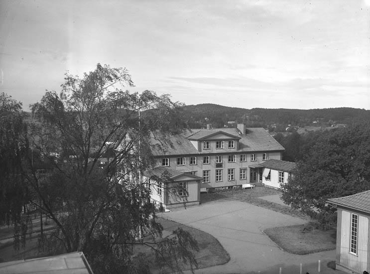 """Text till bilden:""""Långsidan med utbyggnad. Gårdsplan och lövträd. Västkustgården""""."""