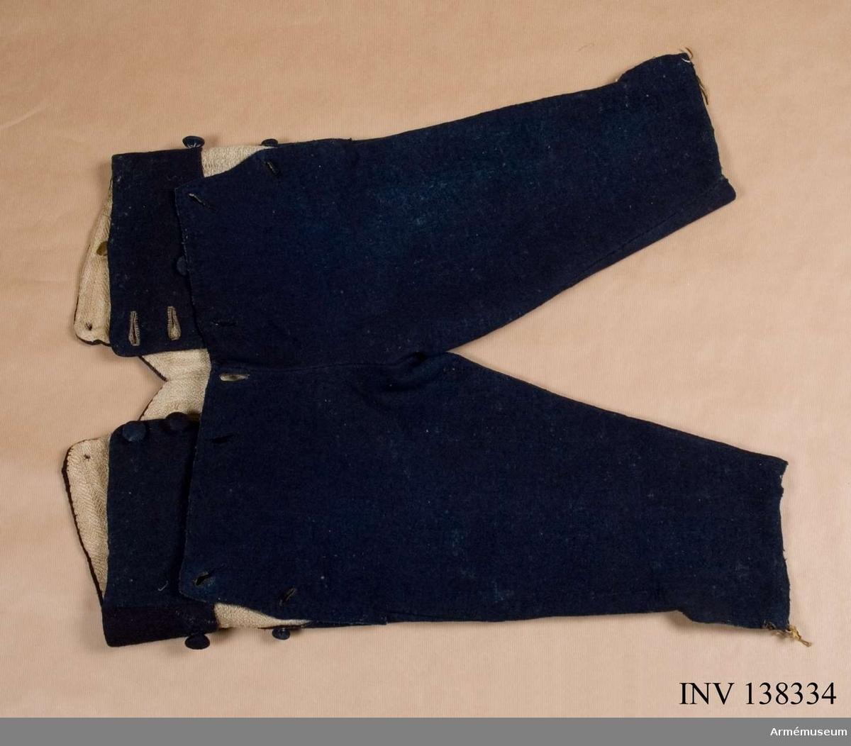 Byxorna är sydda i mörkblått kommisskläde, helfodrade med linne vävt i spetskypert. Knapparna är klädda med mörkblått kommisskläde. Fodret är fastsytt på framsidan med gördeln och täcks av den fodrade luckan som är bred.