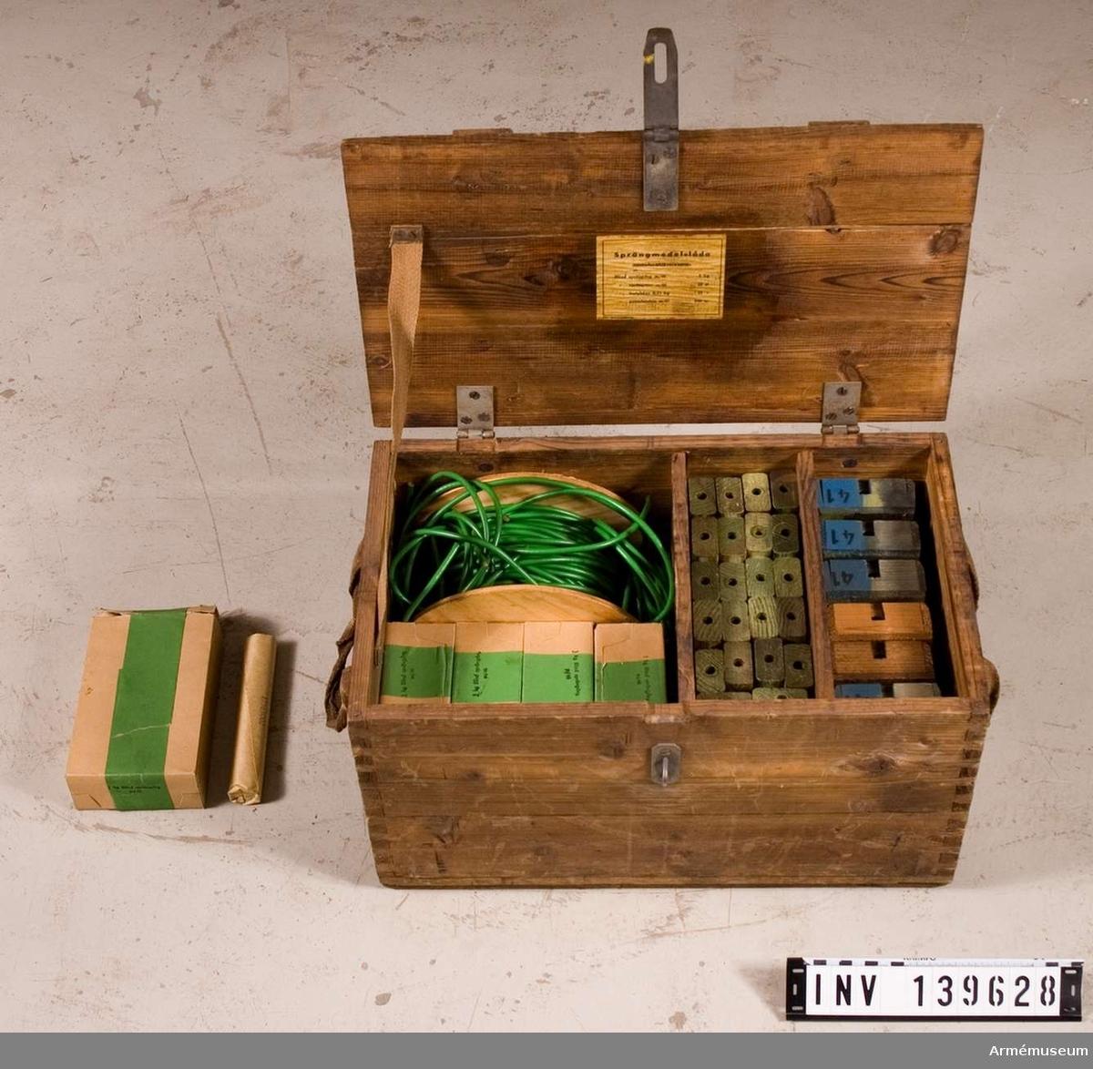 Lådan innehåller: Blind sprängstav m/1946, 22 st, Övningstrampmina m/1946, 6 st, 5 paket á 1 kg blind sprängdeg m/1946, Blind pentylstubin m/1947 på rulle, samt ett antal kortare bitar, varav två med blind sprängpatron.  Enligt etikett på lådans insida ska den innehålla: Blind sprängdeg m/1946, 5 kg, Blind sprängstav m/1946, 23 st, Blind trotylstav 0,25 kg, 23 st, Blind pentylstubin m/1947, 100 m.