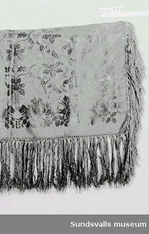 Huvudduk i svart siden med vävt mönster föreställande en bård av rosor och ett mittfält med bladmönster. En röd stämpel i ett hörn med texten '524 Stockholm'. Knuten frans, längd 17 cm.