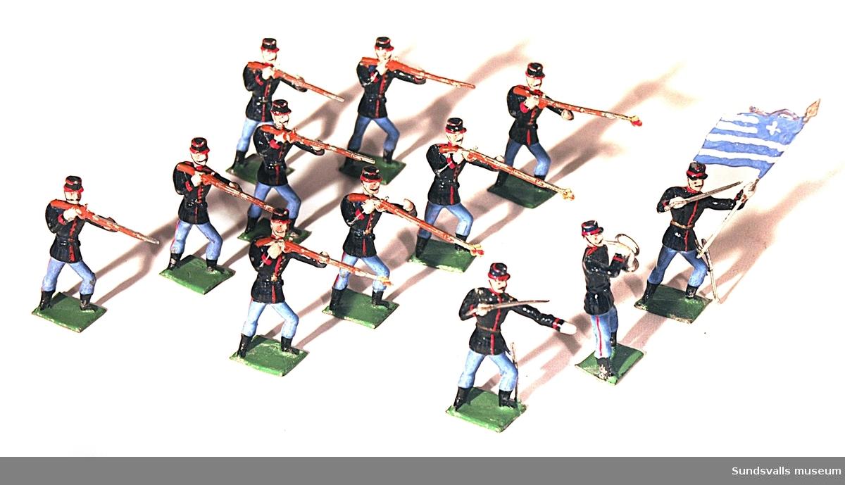 SuM 2753:1-12 tennsoldater. Nio stycken stående med höjda gevär, en stycken med höjd sabel, en stycken fanbärare och en stycken med trumpet. Originalförpackning märkt 'Frans A Santesson, fabrik för Tennleksaker, Stockholm. N. 401 Göta garde'.