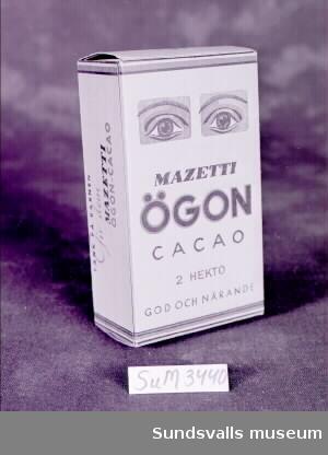 Pappersförpackning för 'MAZETTI ÖGON CACAO'. Förpackningen rymmer 2 hekto. Innehåll saknas.