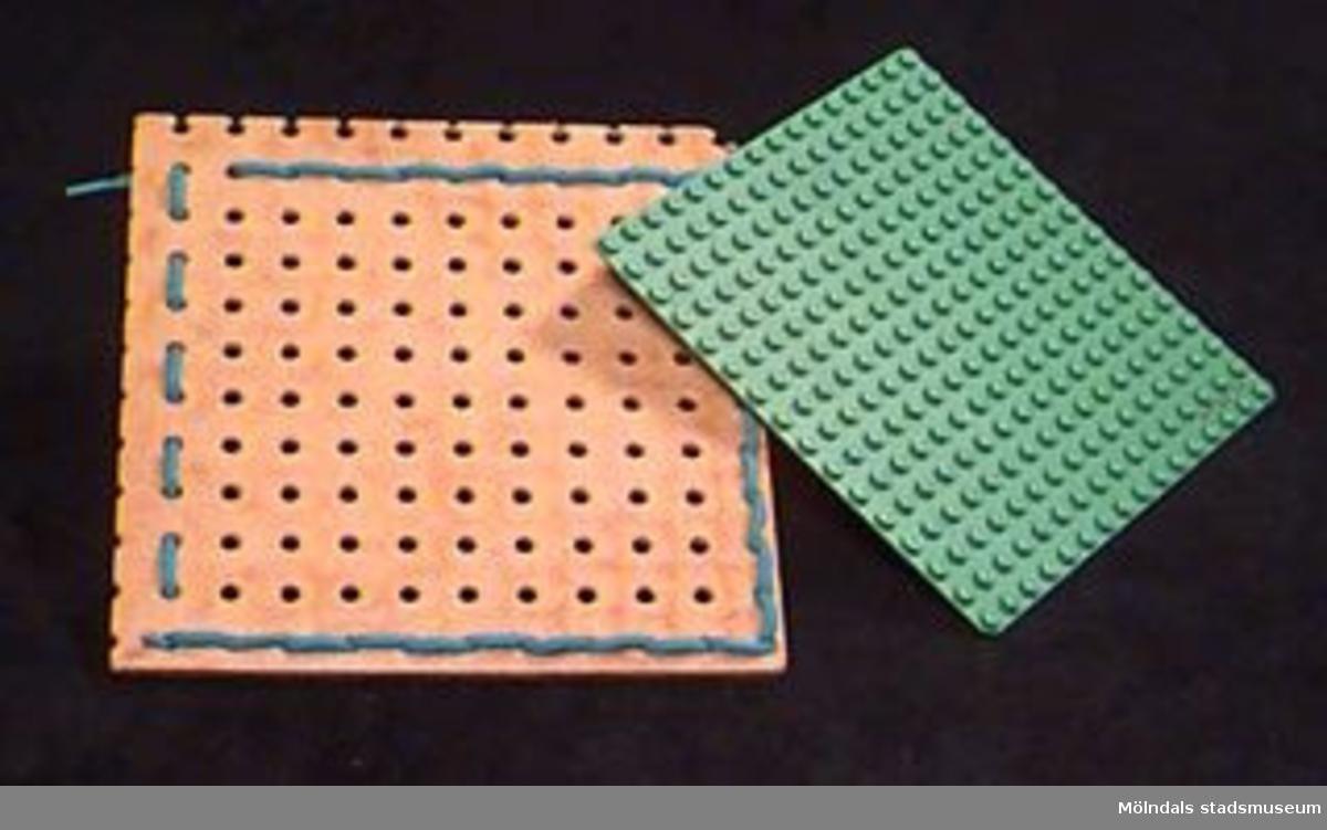 En symmetriskt perforerad masonitbricka/platta som inramats med ett ljusblått skosnöre. L: 150mm. B: 140 mm. Handgjort. En läggplatta i grönt lego. L: 125 mm. B: 125 mm.Anordningen kan användas till diverse små handarbeten av textil karaktär, typ vävmönster, trådmönster etc. Pedagogiskt material för daghem.Gåva av Katrinebergs daghem.