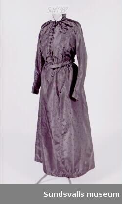 Svart klänning i mönstervävt siden. Livet (SuM 4382:1) är 44 cm långt. Det har upprättstående krage och foder i benvitt. Virkade knappar och platta veck fram. Knäppning fram med hyskor. Kjolen (SuM 4382:2) är 95 cm lång och knäpps bak med hyska och tryckknappar. Smal linning. Ofodrad. Kjolen är fållad med ett brett svart band. Klänningen bars av Margareta Hägglund (1855-1947) vid dottern Olgas bröllop 1918 och vid dotterdottern Karins bröllop 1946.