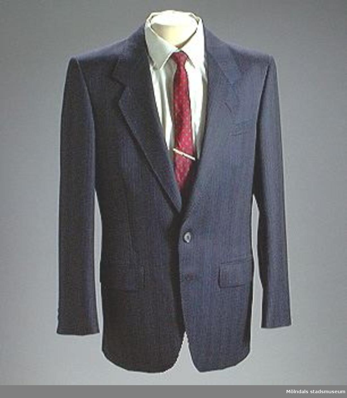 Fullständig kostymutstyrsel, kavaj, byxa, skjorta, slips, slipsnål, skor, sockar.Kavaj MM 02957:1 Mörkblå-randig  enkelknäppt.Byxa        02957:2 Mörkblå-randig.Skjorta     02957:3 vit bommull st. 39 Pierre Cardin.Sips          02957:4 Röd-Blå med prickar San Giovanni.Slipsnål     02957:5 Gulmetall Volvo.Skor         02957:6 Svarta Aristokrat.Sockar      02957:7 Mörkblå.Skänkt i samband med Krinoliner och Kortkort utställningen.