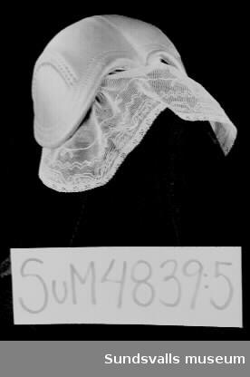 Sundsvalls Martha-förening Hem och samhälles dräkt. Dräkten består av en klänning, ett förkläde, en krage, en brosch och en bindmössa. Klänningen (SuM 4839:1) i ett blårutigt bomullstyg har lång ärm och påsydda vita manchetter. Knäppning fram med hakar och hyskor, samt tryckknapp. V-formad urringning. Förklädet (SuM 4839:2) och kragen (SuM 4839:3) i vitt broderat bomullstyg. Förklädet är 67 cm långt och knyts i midjan. Kragen har triangulär form och fästs fram på bröstet med en brosch. Broschen (SuM 4839:4) bär föreningens emblem och är tillverkad i delvis emaljerad gulmetall och märkt med 'SPORR' på baksidan. Bindmössan (SuM 4839:5) är klädd med ljusblått sidentyg och har vit spets fram och en rosett bak. Dekorationssömmar. Invändigt vitt tyg.