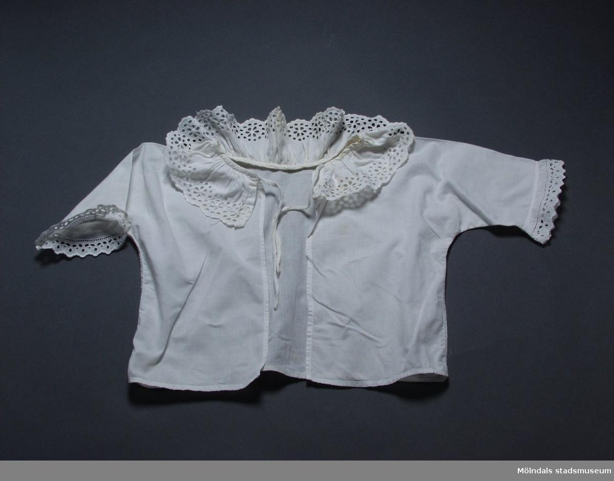 Vit spädbarnsskjorta i bomull med brodyr runt halsringning och ärmar.