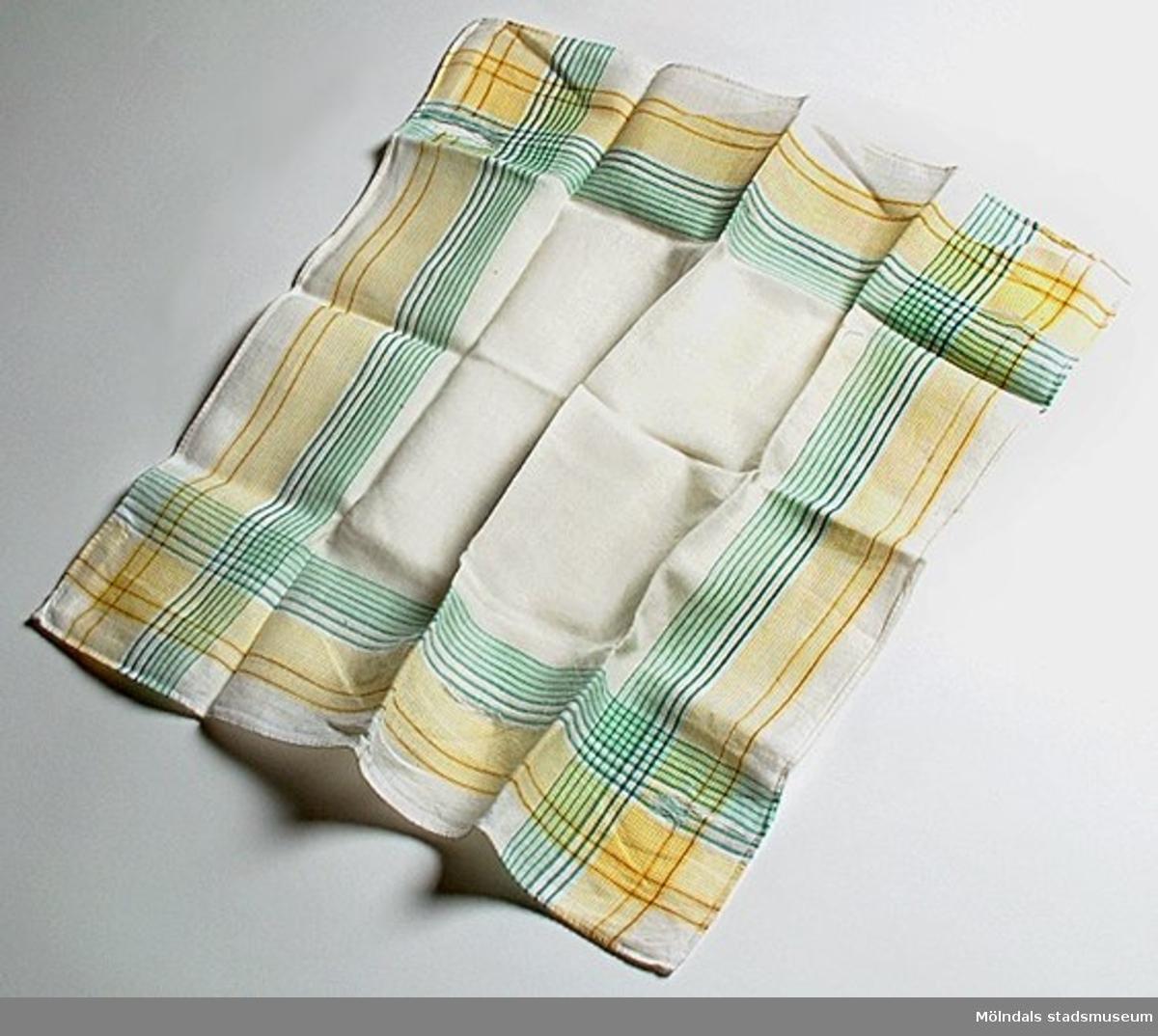 Barnnäsduk av  bomullsbatist, Vit i mitten och med gul och grönrutiga kanter, samt ett K broderat i vitt i ett av hörnena.  Näsduken är trasig på några ställen, väl använd.Som barn skulle givaren alltid ha en ren näsduk i fickan. Ju mer tvättad den blev, desto mjukare och skönare var den att använda - ända tills den gick sönder.