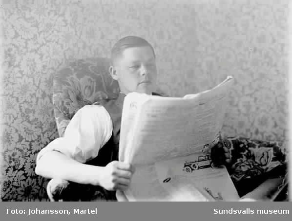 Man som sitter i fotöljen och läser tidning.