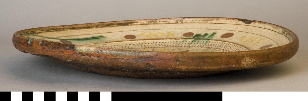 Fat av lera med engobe av piplera, skraffering, brun och grön glasyr. Brätten prydd med nio runda bruna prickar. Runt spegel hemnring.På spegel en stängel med tre blommor. På sidorna årtalet 1751.