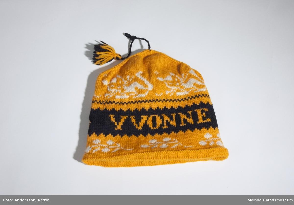 """Mössa som användes av givaren Yvonne Jonsson under 1970-talet.Mössan är orange i botten och har ett mönster aom går i vitt, svart och orange. På framsidan finns namnet """"YVONNE"""" stickat som en del av mönstret. Mössan har också en tofs mitt på huvudet som sitter fast i en svart garntråd. Tofsen går i färgerna svart och orange.MåttHöjd: 278 mm, Diam: 250 mmTofs med tråd, Längd: cirka 180 mm (med knut)Det är givarens mor Gullan Svensson som stackade mössan. Gullan stickade även sådana här """"namn""""-mössor till övriga i familjen, så alla fick en mössa med sitt namn på."""