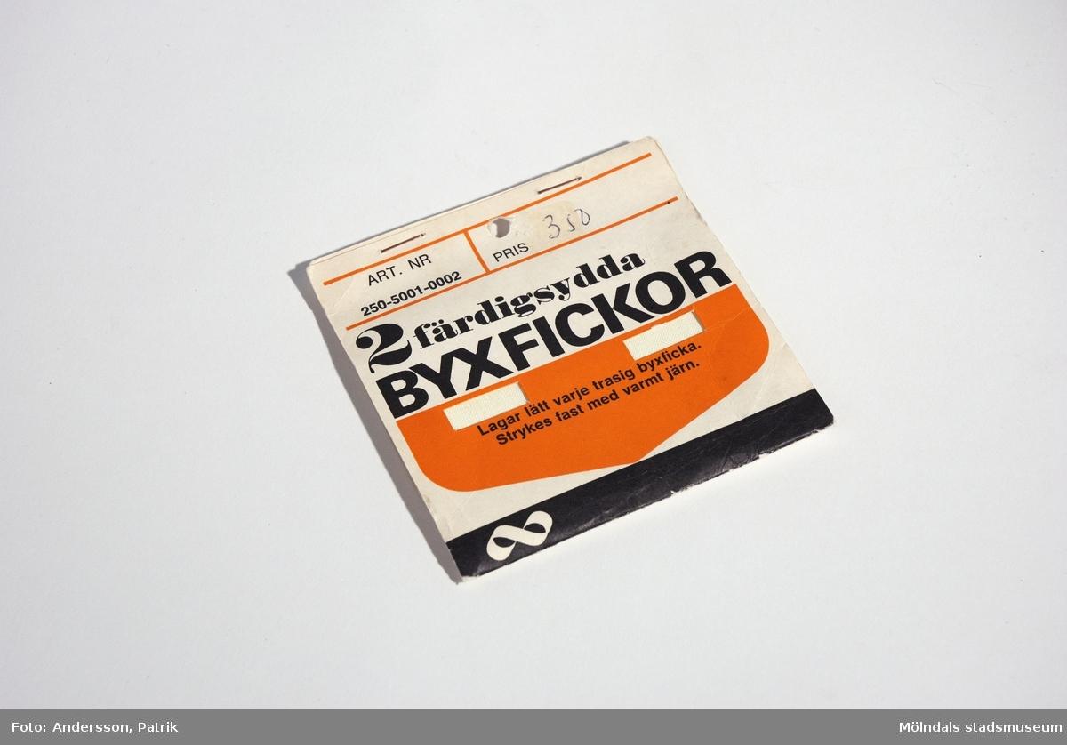 """1 st byxficka i förpackning från 1960-talet.Ena fickan är använd, därför ligger det bara en byxficka kvar i förpackningen.Byxfickan är vit och ligger ihopvikt i en förpckning av papp. Förpackningen går i färgerna vitt, svart och orange. På framsidan står texten:""""ART. NR 250-5001-0002PRIS 3 502 färdigsydda BYXFICKORLagar lätt varje trasig byxficka.Strykes fast med varmt järn."""" samt Kooperativa förbundets logga. På förpackningens baksida finns beskrivning och teckningar på hur man sätter fast fickan i byxorna.Mått på ficka: Längd: 184 mm, bredd: 137 mm."""