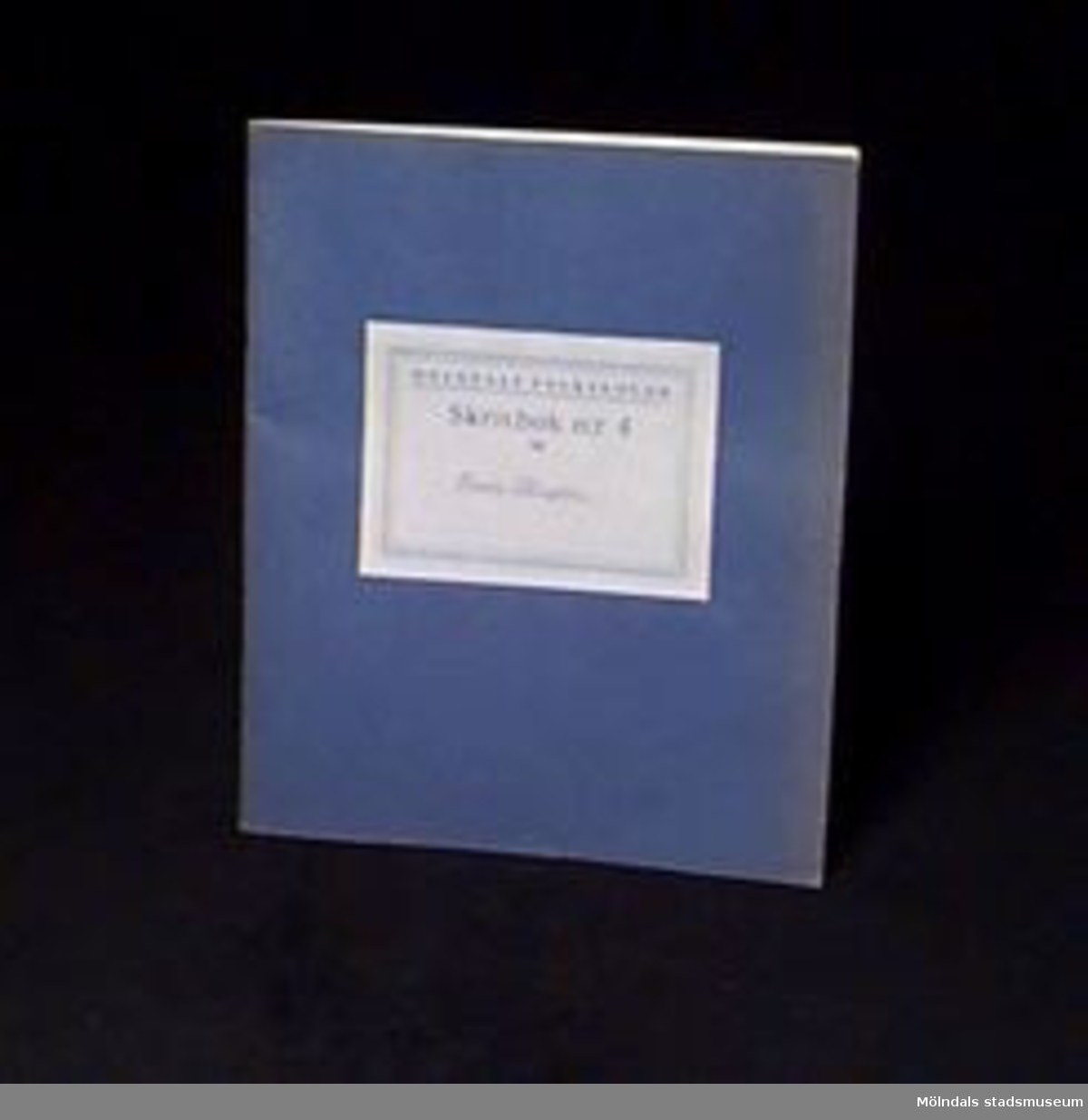 """Blå skrivbok med linjerade sidor. På omslaget en etikett med """"MÖLNDALS FOLKSKOLOR/Skrivbok n:r 4 för"""" samt skrivet med blyerts: """"Rune Olsson"""". Givaren gick hela sin skoltid i Toltorpsskolan."""