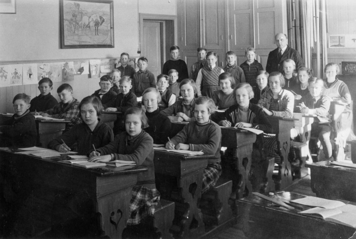 Gruppfoto med flickor och pojkar i klassrummet på Gamla Fässbergsskolan. Magister Daniel Nilsson med elever. 5:e - 6:e klass. Radion på väggen har eleverna samlat in pengar till.Fässbergsskolan låg i sydvästra Solängen och var en av Mölndals tre äldsta skolor, byggd i början av 1860-talet. Byggnaden brändes ned 1971.