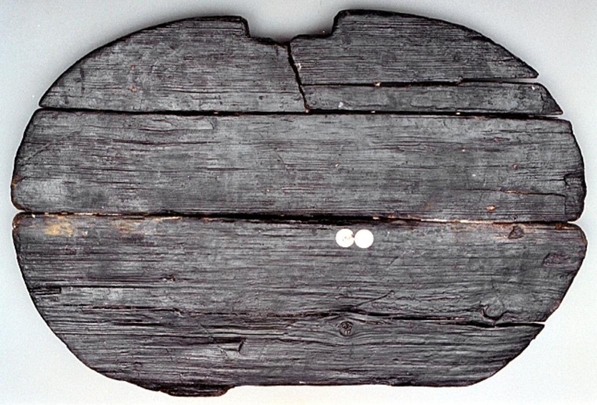 Del av lock till en laggad träbalja. Locket utgörs av tre sammanfogade delar. På lockets ovansida, tvärsöver, löper ett nedsänkt spår där en regel sitter. Föremålet är sprucket på två ställen och består av tre delar. Två av delarna sitter på plats med hjälp av regeln. Den tredje delen är lös och har fått ett nytt fyndnummer.