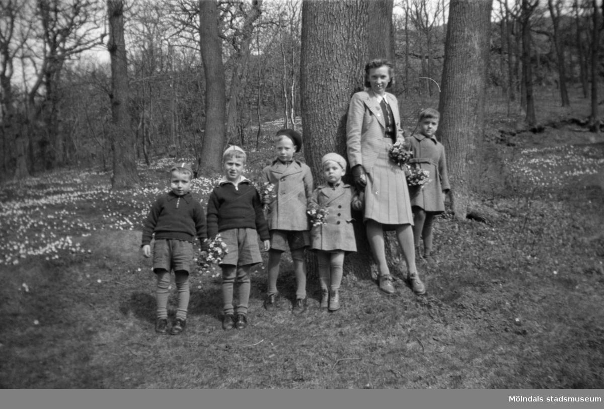 """Barn med vårdare i vitsippshage. Mölndals barnhem  (f.d. Holtermanska) Rudbergsgatan.  Direktören Martin Holterman i Ostindiska kompaniet ägde Åby gård. 1782 skänkte han 3000 daler silvermynt till Fässbergs församling + ett nybyggt skolhus och trädgård på gårdens ägor vid Åby by. I skolan skulle 10 fattiga barn undervisas i """"kristendom, skrivande och något räknande. Holtermans skola fanns kvar till 1875. Då hade donationens ändamål ändrats, och man byggde i stället ett barnhem kombinerat med småskola. 1914 brann barnhemmet och 1915 byggdes ett nytt barnhem på samma tomt. 1929 överlämnades barnhemmet till Mölndals stad."""
