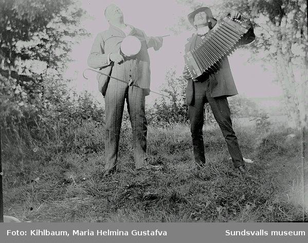 Porträtt i utemiljö. En man spelar dragspel, en man sjunger.