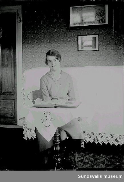 Porträtt. Kvinna i rumsmiljö, sitter vid ett bord med ett fotoalbum uppslaget.