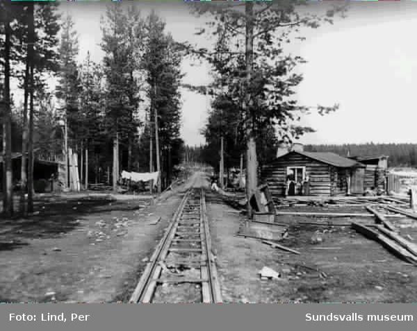 Alby 1898. Till vänster och höger i bild arbetarbostäder i mitten av bilden ett spår. Till höger två kvinnor.