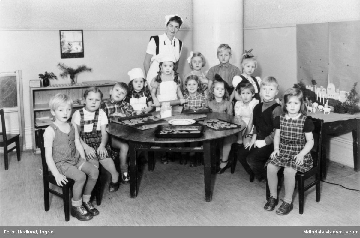 Bosgårdens barnträdgård 1938-1945. Fröken och barn som står uppställda bakom ett runt bord inför fotografering.